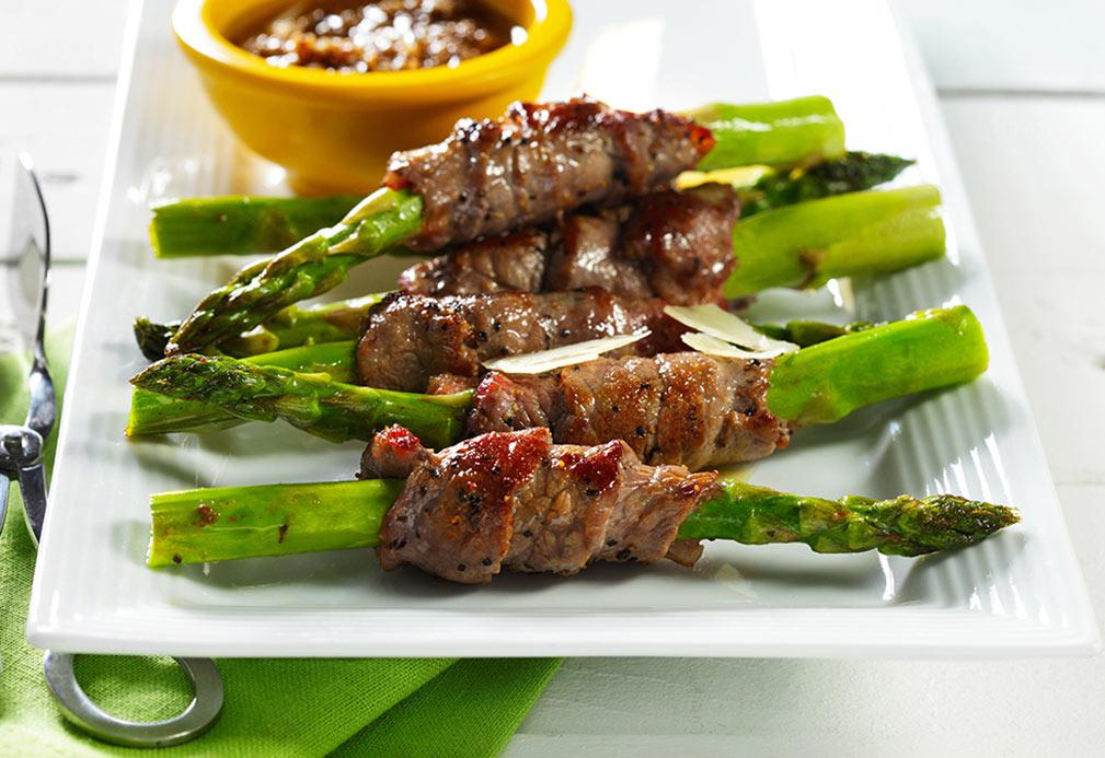 Tallos de espárragos envueltos en carne de res con salsa de ajonjolí y chipotle