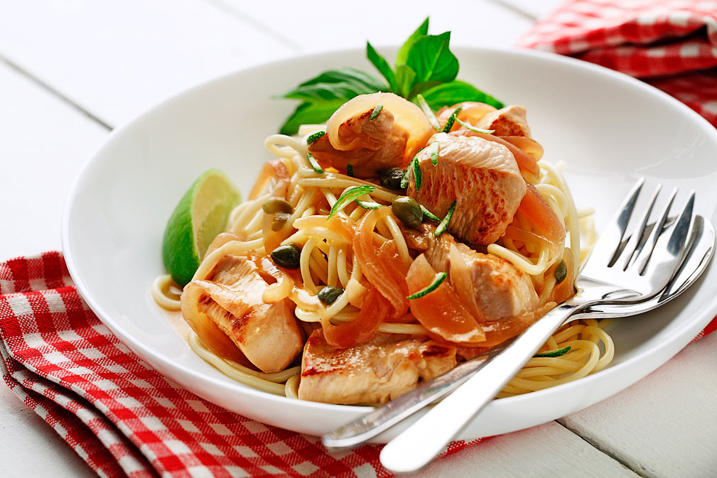 Pollo sofreído con limón y alcaparras sobre espagueti